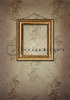 Gold frame hangs on an old wall.
