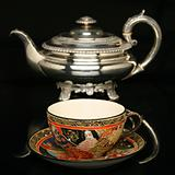 Silver teapot and an antique chinese cup of tea