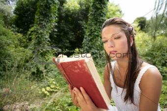 Beautiful woman reading a book in forest, nature