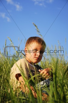 Young boy sitting on green grass