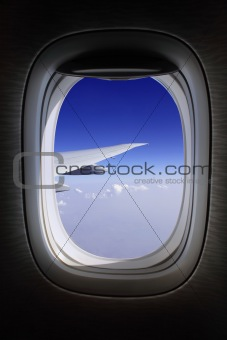 aeroplane window with blue skies