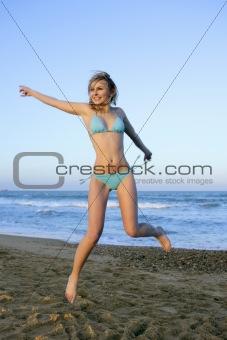 Beautiful blond girl jumping on the beach