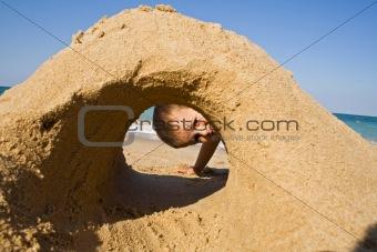 Boy looking through a sand castle on the beach