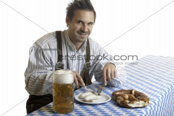 Bavarian Guy wearing leather trousers (lederhose) having meal at