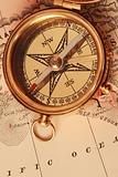 Antique brass compass over old map