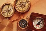 Four antique compasses over old background