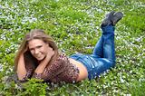 Cheerful girl on the green flowered meadow