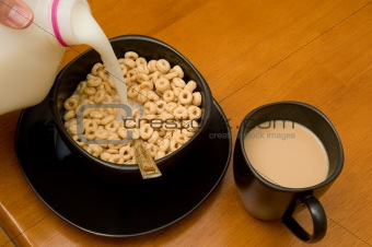 Breakfast consisting of cereal with milk and coffee with cream