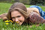 pretty girl smells dandelion on the green meadow
