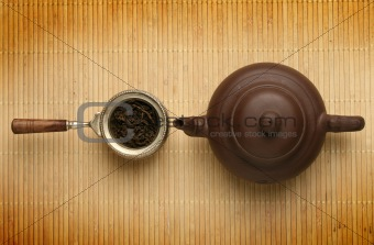 Antique teapot and a scoop with tea leaves
