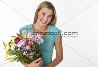 A young woman is holding a boquet of flowers