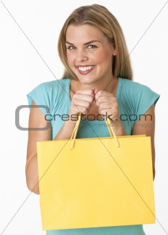 A young woman is holding a shopping bag
