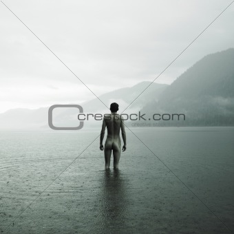 Young naked man in lake
