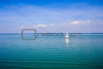 Blue landscape with sailboat