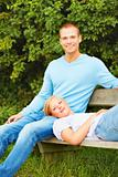 Young couple relaxing on a bench at the park