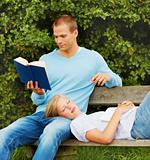 Young man reading a book in the park while girlfriend sleeping on his lap