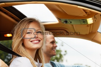 Happy young couple enjoying a drive in new car
