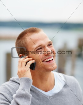 Happy handsome young guy talking on a cellphone