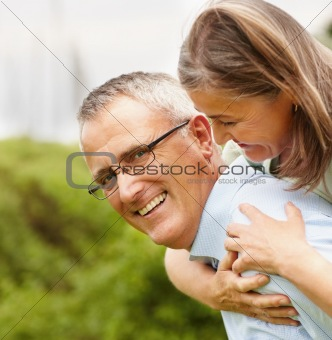 Happy senior man piggybacking his wife in park