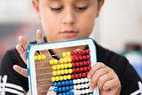 Schoolboy calculate with abacus
