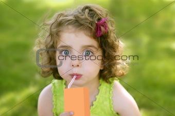 Little girl drinking juice from an orange brik