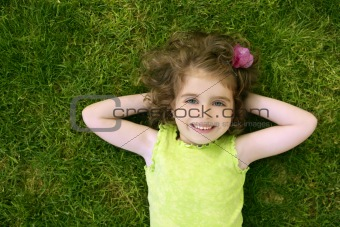 Beautiful little toddler girl happy lying on grass