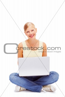 Young female sitting on the floor and using a laptop