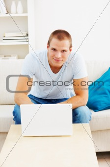 Young man working on a laptop at home