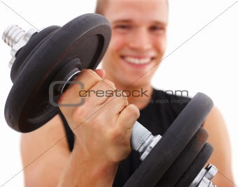 Happy young man exercising with dumbbell