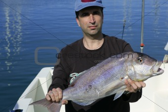 Fisherman showing proud catch saltwater fish