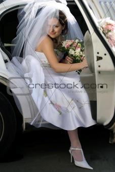 Smiling bride in wedding car limo
