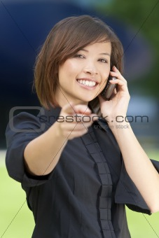 Beautiful Oriental Woman on Her Smart Cell Phone and Pointing