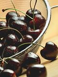 Dark cherries in steel mesh sieve on wooden table under warm lighting