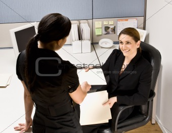 Businesswoman handing co-worker file folder