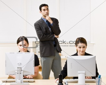 Businessman watching co-workers work