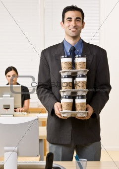 Businessman carrying tray of coffee