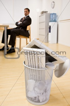 Computer monitor and keyboard in trash basket