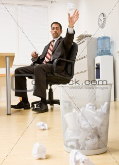 Businessman throwing paper in trash basket