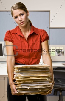 Businesswoman carrying stack of file folders