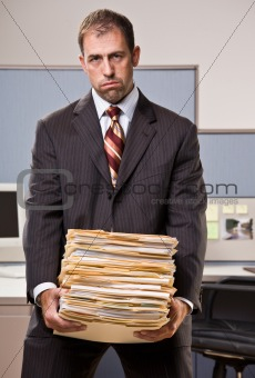 Businessman carrying stack of file folders