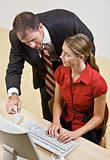 Businessman helping co-worker at computer