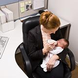 Businesswoman feeding baby at desk