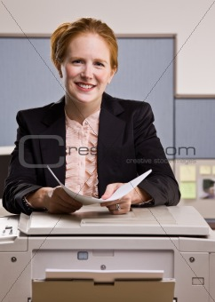 Businesswoman copying papers in office