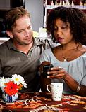 Mixed race couple in coffee house with cell phone