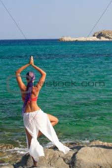Beautiful girl meditating on the beach