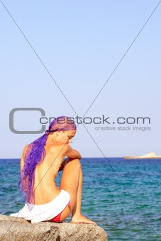 Beautiful girl meditating on the beach