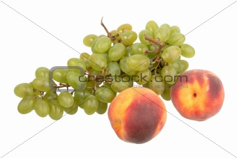 Green grapes bunch and two orange peach.