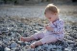 Little baby sitting on the stones