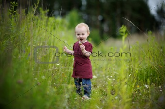 Little baby in a meadow eating cookie