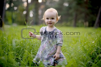 Smiling baby girl in a meadow
